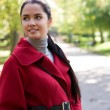 Young pretty woman in red coat at the autumn park. — Stock Photo