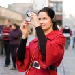 Young woman with headphones, listening to audio guide taking pic - Stock Photo