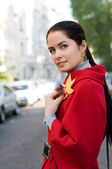 Young women in red coat on the street — Stock Photo