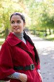 秋の公園で赤いコートの若いきれいな女性. — ストック写真