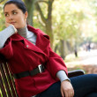 Young Caucasian woman sitting in a park on a wooden bench, — Stock Photo
