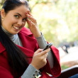 Young Caucasian woman with a cell phone, sitting in a park — Stock Photo #4911168