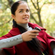 Young Caucasian woman with a cell phone, sitting in a park - Stock Photo