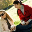 Two young women having coffee break together in park - Stock Photo