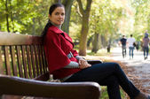 Young Caucasian woman sitting in a park on a wooden bench, — Stock fotografie