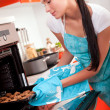 Beautiful brunette woman in the kitchen baking cookies. — Stock Photo