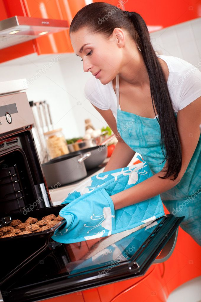 Beautiful brunette woman in the kitchen baking cookies. — Stock Photo #5047951
