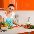 Woman cutting vegetables in modern kitchen interior — Stock Photo #5235445