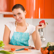 Young woman in her kitchen cutting ingredients — Stock Photo