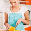 Foto de Stock  : Young woman cutting vegetables in a kitchen