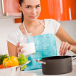 Beautiful young woman cooking in the kitchen, tasting soup — ストック写真