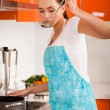 Beautiful young woman cooking in the kitchen, tasting soup — Stock fotografie