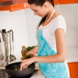 Beautiful young woman cooking in the kitchen — Stock Photo