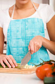 Woman cutting vegetables in modern kitchen (shallow DOF) — Stock Photo