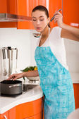 Beautiful young woman cooking in the kitchen, tasting soup — Stock Photo