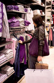 The woman buys clothes in shop — Stockfoto