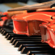 The violin lies on keys of the piano — Stock Photo