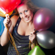 Smiling woman on party holding balloons - Stock Photo