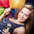 Smiling woman holding new year's champagne and balloons — Stok fotoğraf
