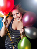 Smiling woman on party holding balloons — Stock Photo