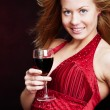 Smiling young woman with sylvester champagne over dark — Stock Photo