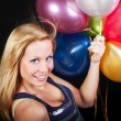 Smiling woman on party holding ballons - Stock Photo