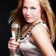 Woman holding champagne over dark — Stock Photo