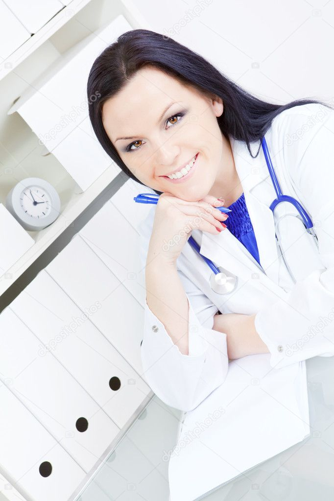 Smiling doctor woman with stethoscope sitting  in office  Stock Photo #4258210