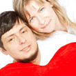 Happy couple holding red heart pillow over white — Stock Photo