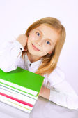 Girl sitting near table with books — Stock Photo