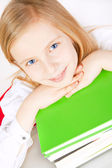 Small girl with books on table — Stock Photo