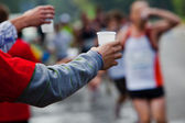 Runner take a water in a marathon race — 图库照片