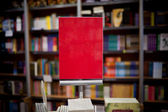 Red ad space in bookstore - many books in the background — Stock fotografie