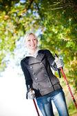 Woman training Nordic Walking in autumn scenery — Stock Photo