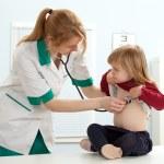 Doctor pediatrician examining little girl — Stock Photo