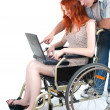 Man, woman keeping laptop on wheelchair — Stock Photo
