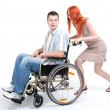 Man on wheelchair woman push trolley - Stock Photo