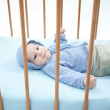 Baby boy lying in crib - Stock Photo