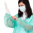 Doctor pulling on surgical gloves — Stock Photo #3935718
