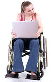 Woman with laptop on wheelchair — Stock Photo