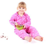 Eating little girl in pink pajamas — Стоковое фото