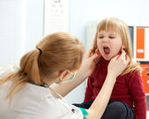 Doctor pediatrician examining baby mouth — Stock Photo