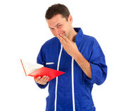 Man in blue coveralls with book — Stock Photo
