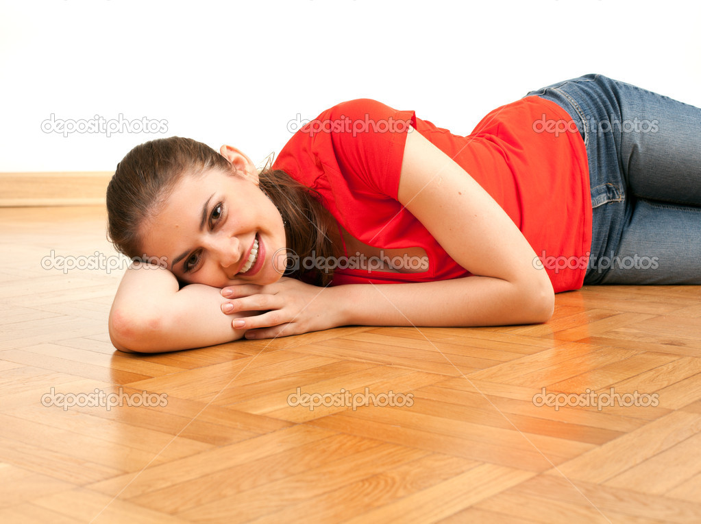 Smiling young woman lying on the wooden floor — Stock Photo #3932414
