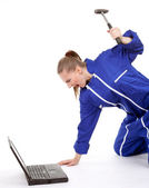 Angry woman with hammer and laptop — Stock Photo
