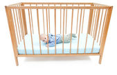 Baby boy lying in crib — Stock Photo