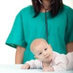 Woman doctor exams baby — Stock Photo