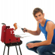 Young man grilling chiken — Stockfoto