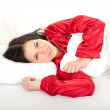 Woman in red pajamas in bedding — Stock Photo #4406879