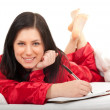 Writting on clipboard woman in pajamas — Stock Photo